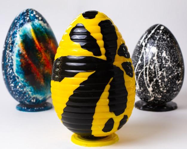 Ovo de chocolate amarelo vista frontal com um hieróglifo preto em stand com outros dois ovos de chocolate