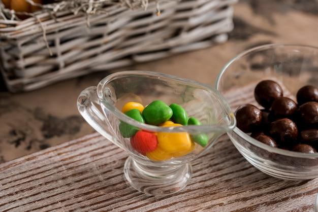 Ovo de chocolate saboroso de sobremesa de páscoa com drageias de doces de cor na mesa de madeira