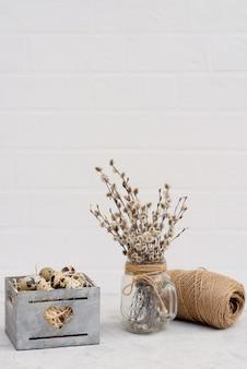 Ovo de codorna em uma cesta de madeira com galhos de salgueiro frescos e um rolo de flagelo.