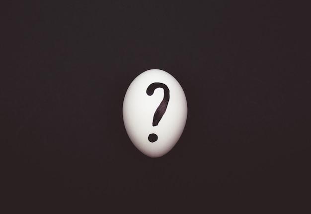 Ovo de galinha branca com um ponto de interrogação abstrato desenhado em um fundo preto. ideia criativa de nutrição natural saudável.