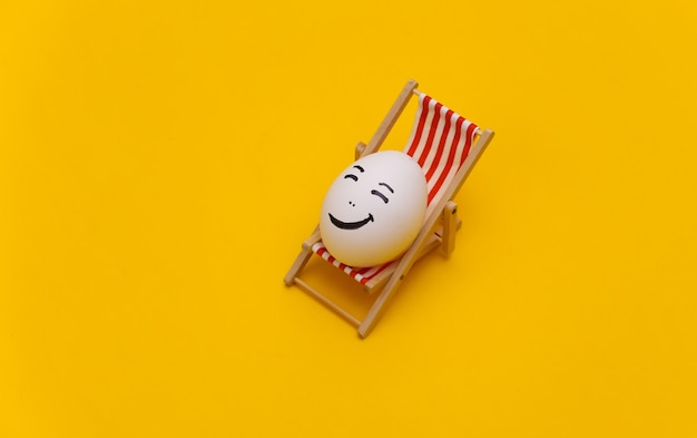 Ovo de galinha com mão desenhada cara feliz na espreguiçadeira da praia. fundo amarelo. descanso de verão, conceito de viagem