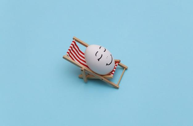Ovo de galinha com mão desenhada cara feliz na espreguiçadeira da praia. fundo azul. descanso de verão, conceito de viagem
