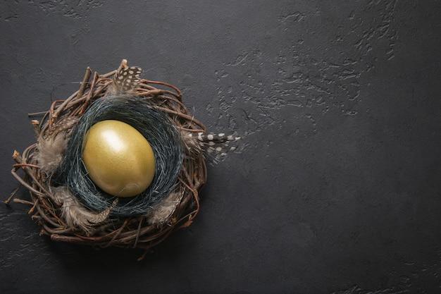 Ovo de galinha dourada no ninho na mesa preta