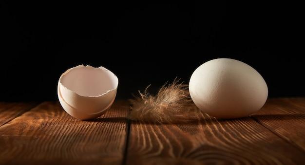 Ovo de galinha e cascas de ovo em uma mesa de madeira em um escuro.