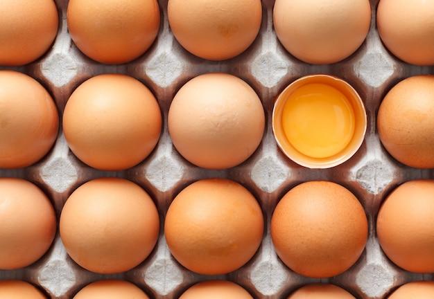 Ovo de galinha é meio quebrado entre outros ovos marrons