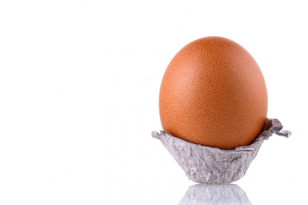 Ovo de galinha em papelão rasgado, sobre um fundo branco e isolado. a clara de ovos orgânica marrom na superfície do espelho, fim da galinha acima.