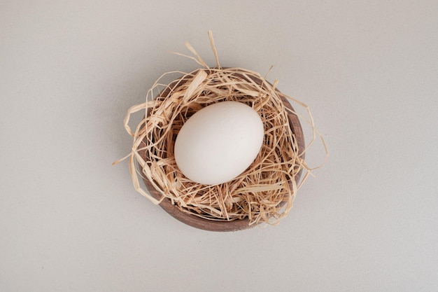 Ovo de galinha fresca com feno em uma tigela de madeira.