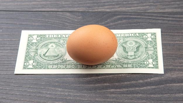 Ovo de galinha no fundo do dólar em um fundo de madeira.