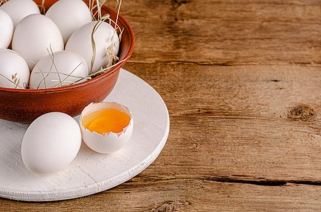 Ovo de galinha quebrado com gema crua na mesa de madeira. copie o espaço