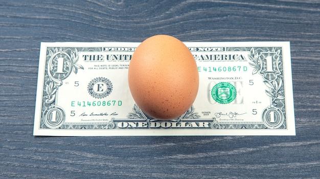 Ovo de galinha sobre o dólar em uma mesa de madeira. venda de produtos alimentícios