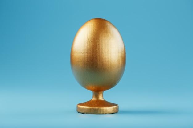 Ovo de ouro sobre um fundo azul com um conceito minimalista. espaço para texto. modelos de design de ovo de páscoa. decoração elegante com conceito mínimo.