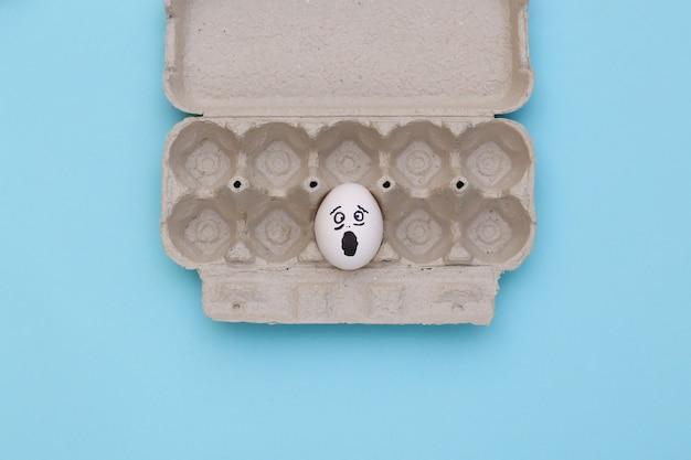 Ovo de pânico com rosto desenhado à mão na bandeja de ovos sobre fundo azul