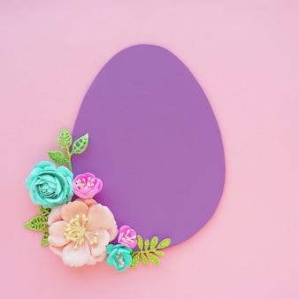 Ovo de papel lilás em um fundo rosa e flores artificiais e folhas de papel. espaço para texto. conceito de páscoa