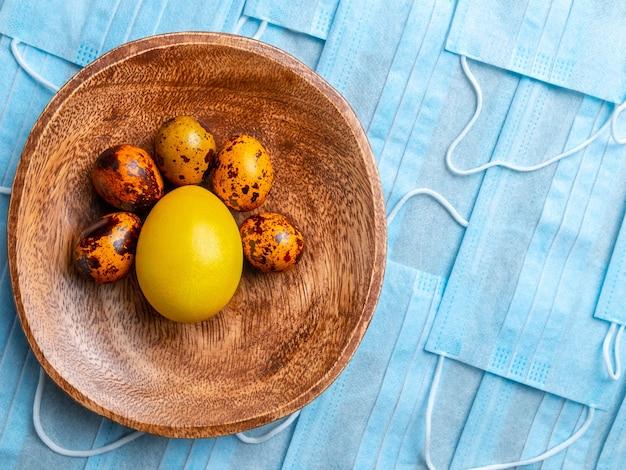 Ovo de páscoa amarelo e ovos de codorna em uma tigela sobre um fundo de máscaras médicas azuis.