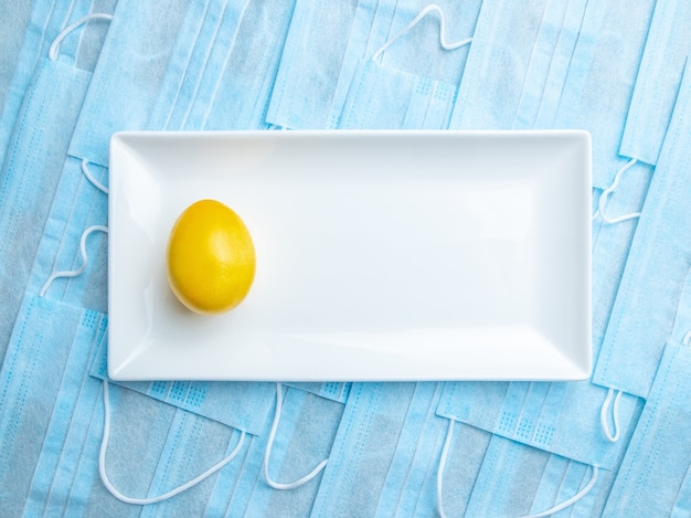 Ovo de páscoa amarelo em uma placa de cerâmica branca em um fundo de máscaras médicas azuis
