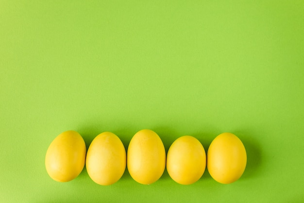 Ovo de páscoa amarelo sobre fundo verde brilhante