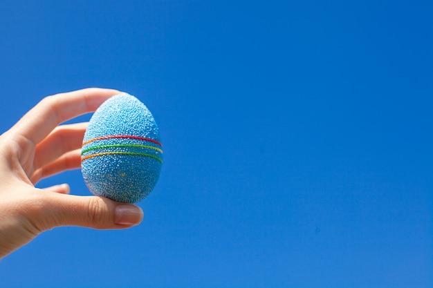 Ovo de páscoa bonito brilhante na mão no fundo do céu azul