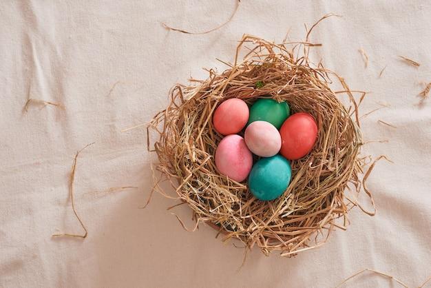 Ovo de páscoa bonito com várias cores em palha com fundo de madeira, conceito de dia de páscoa.