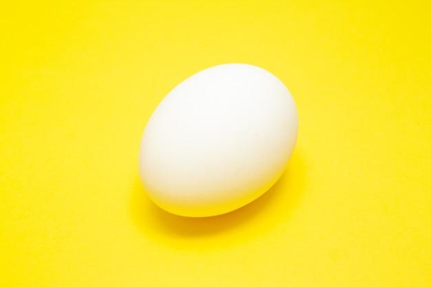 Ovo de páscoa branco sobre fundo amarelo no centro