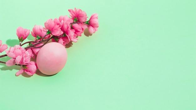Ovo de páscoa colorido com flores na mesa