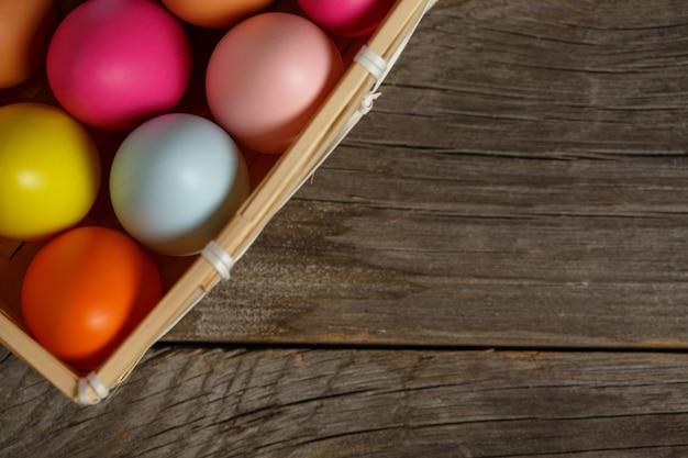 Ovo de páscoa colorido no ninho na mesa de madeira