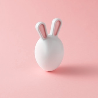 Ovo de páscoa com orelhas de coelho em um fundo rosa. um conceito criativo de páscoa.
