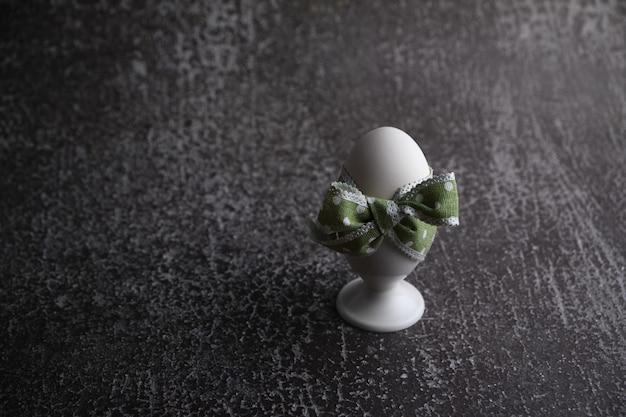 Ovo de páscoa cozido com laço verde no suporte em fundo escuro