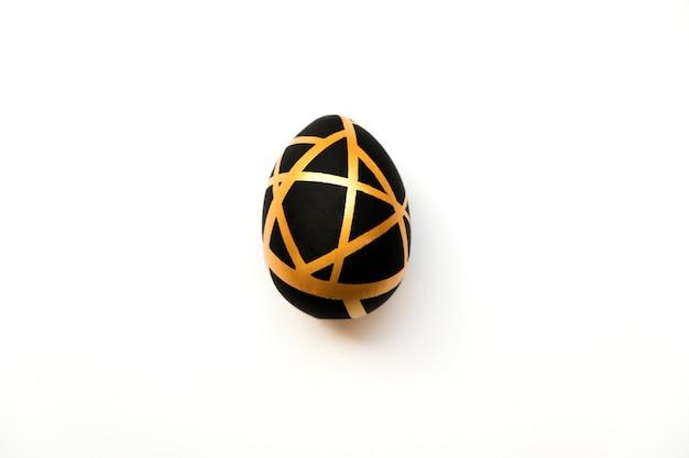 Ovo de páscoa dourado com padrão preto geométrico isolado no fundo branco