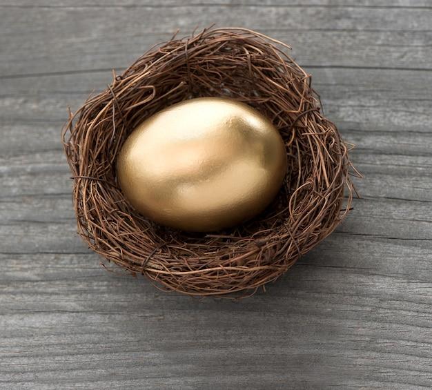 Ovo de páscoa dourado em ninho de pássaros em fundo de madeira vintage. foco seletivo