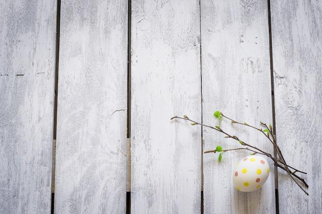 Ovo de páscoa e galhos com folhas jovens em pranchas de madeira rústicas