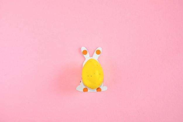 Ovo de páscoa e silhuetas de papel de um coelhinho da páscoa em fundo rosa