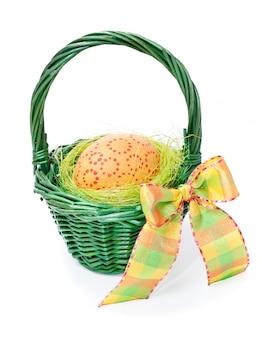 Ovo de páscoa em uma cesta de palha verde no branco