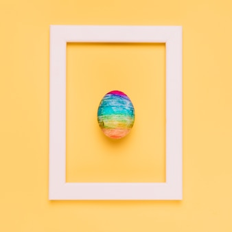 Ovo de páscoa multicolorido dentro da moldura de borda branca em pano de fundo amarelo