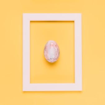 Ovo de páscoa na armação de borda branca contra um fundo amarelo