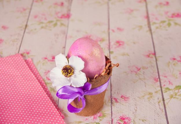 Ovo de páscoa rosa em uma panela no fundo floral