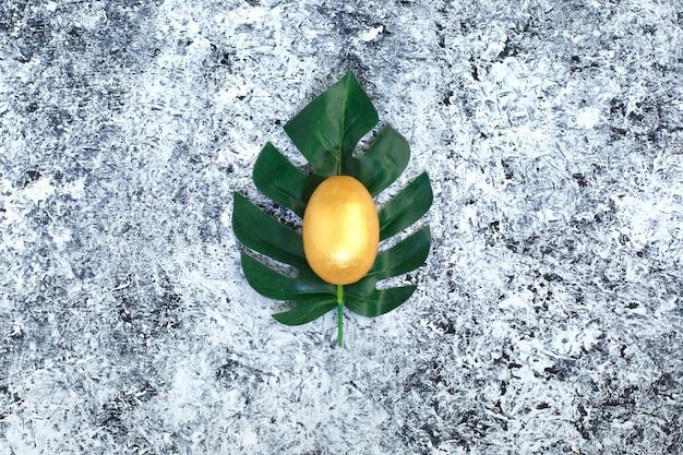 Ovo dourado em uma folha verde, um símbolo de fazer o dinheiro e investimento bem sucedido no fundo preto e branco abstrato.