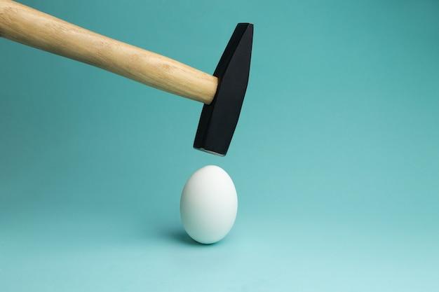 Ovo e martelo pairando sobre ele, antes do golpe. um ovo e martelo no azul