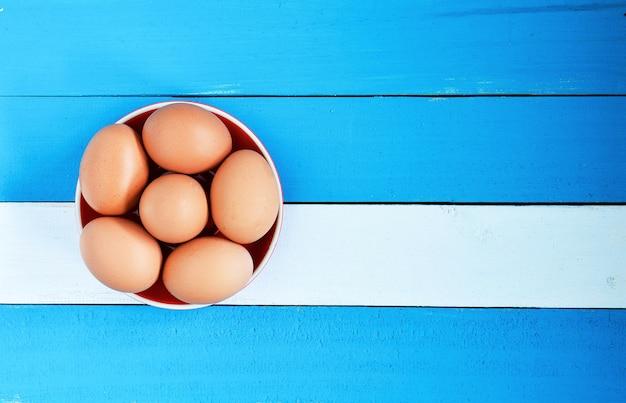 Ovo em uma tigela sobre fundo azul de madeira