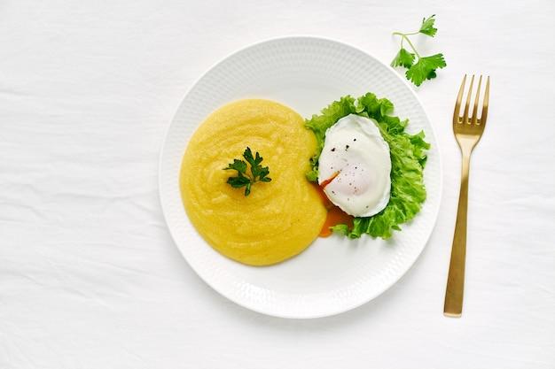 Ovo escalfado e polenta com salada de alface