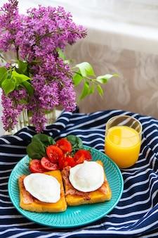 Ovo escalfado em torrada inglesa torrada com espinafre, tomate cereja, suco de laranja