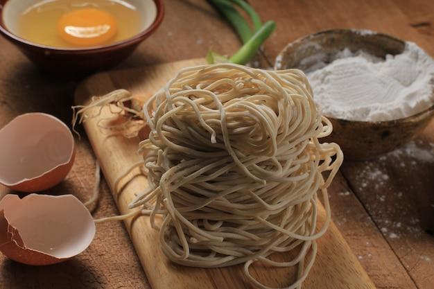 Ovo, farinha e macarrão asiático cru na tábua de madeira