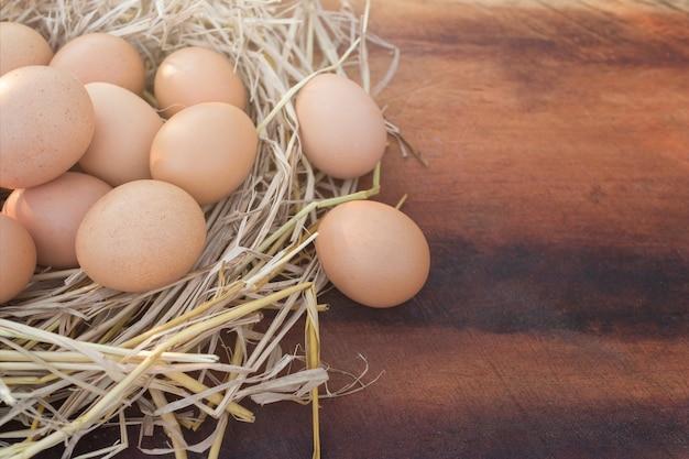 Ovo fresco da galinha em um ninho e ovos marrons em uma tabela de madeira, imagem com espaço da cópia.