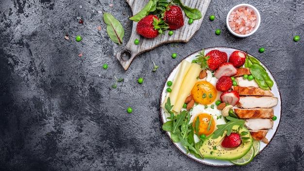Ovo frito, abacate, morango, filé de frango grelhado, queijo, nozes e rúcula. dieta ceto. café da manhã ou almoço saudável. vista do topo. copie o espaço.