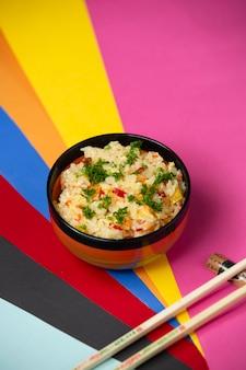 Ovo frito arroz com pimentão e endro em fundo colorido