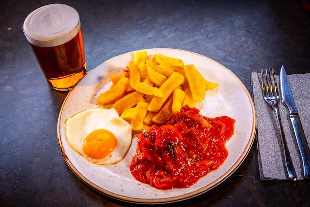 Ovo frito com batata, cerveja e pimentão vermelho em um fundo preto, em um prato azul