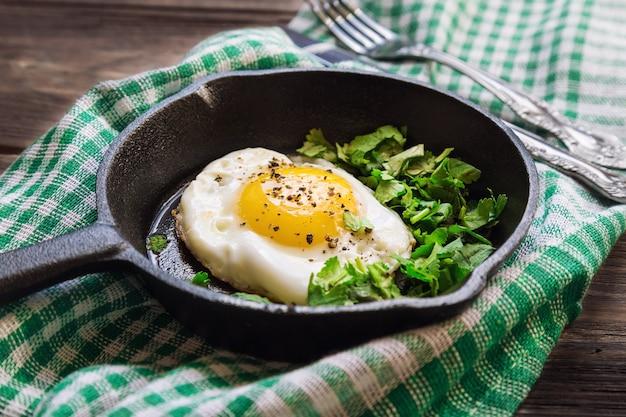 Ovo frito com coentro na frigideira de ferro em fundo de madeira rústica café da manhã tradicional