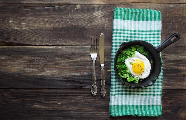 Ovo frito com coentro na frigideira de ferro em fundo de madeira rústico café da manhã tradicional