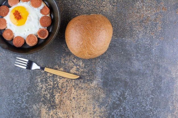 Ovo frito com linguiça na frigideira servido com pão de forma