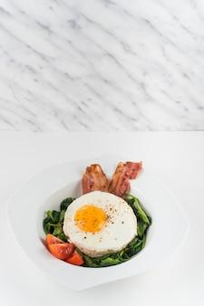 Ovo frito com salada e bacon no prato sobre a mesa contra o pano de fundo texturizado de mármore