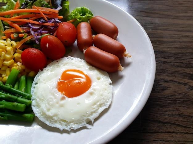 Ovo frito com salsichas e legumes no prato branco, como tomate vapor de milho espargos